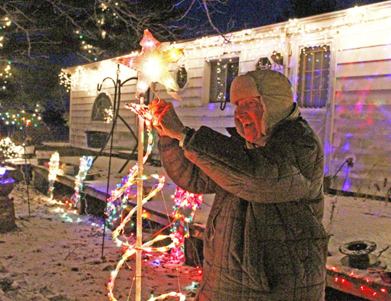 Photo by Mike Brothers Paul Feist has decorated his home southeast of Sullivan since 1959. Above he puts the finishing touches to the display that may be seen from the city limits.
