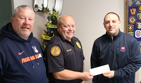 Photo by Mike Brothers Sullivan IGA manager Pat Stinson (right) presents $500 check to Moultrie County Secret Santa representatives Police Chief Jim Waggoner and Greg Foster.